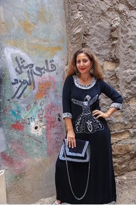 """Picture of Our handmade embroidered """"Dervishes"""" galabeya is an awesome blend of fun and elegance!!! No more accessories needed other than our 'B U"""" black clutch embellished with silver sequins."""